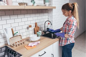 Woman washing frying pan over sink in kitchen