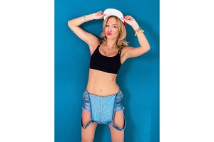 Young blonde girl posing wearing urban clothes sports bra swag baseball cap or hat
