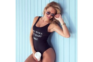 Sexy blonde woman in bodysuit with perfect body wearing sunglasses standing near wall cup of coffee looking down