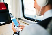 Mature businessman with smartphone travelling by train.