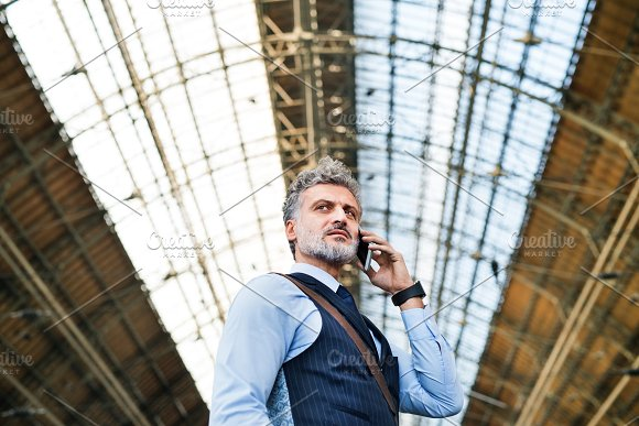 Mature businessman with smartphone on a train station. in Graphics