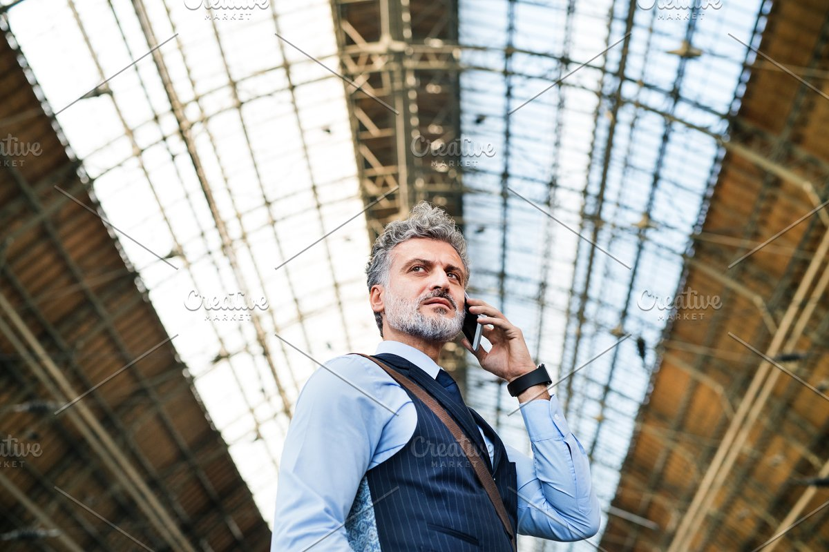 Mature businessman with smartphone on a train station. in Graphics - product preview 8