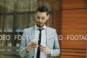 Stedicam shot of cheerful businessman using smartphone and walking in modern office hall