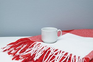 Cup of coffee on red and white plaid