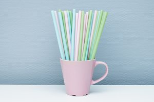 Pink cup filled with colored straws