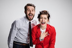 The business man and woman laughing on a gray background