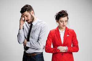 The sad business man and woman conflicting on a gray background