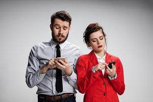Business concept. The two young colleagues holding mobile phones on gray background