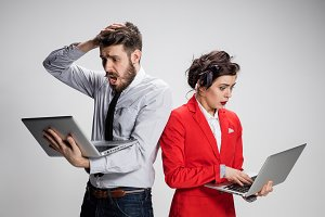 The young businessman and businesswoman with laptops  communicating on gray background