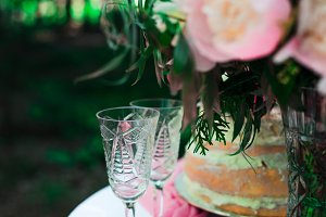 two glasses on the table on the background of flowers and cake. wedding ceremony