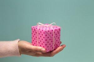 Woman's hand & pink gift polka dots