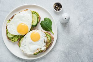 Two toasts with avocado and egg