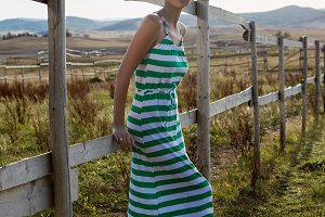 girl in long green dress in the village at the fence in the morning