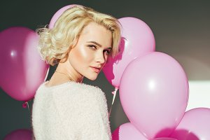blonde girl with pink balloons