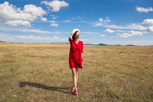 sexy girl in red dress standing in a field in autumn