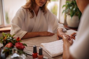 Woman in salon receiving a manicure