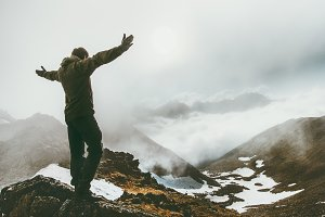Raised hands Man in foggy mountains