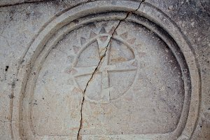 Closeup of a marble relief Maltese cross on a stone wall of an ancient Sicilian church.