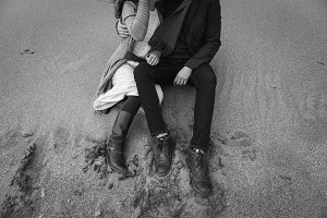 legs of stylish couple on sand