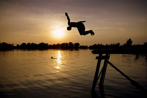 Boy jumps to the lake in sunset