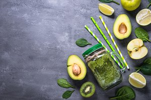 Healthy green smoothie in mason jar and ingredients.