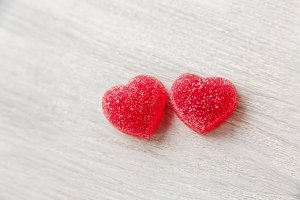 Two red heart shaped candies.