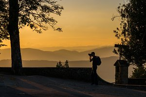 Man taking photo of sunset against  mountains on the background