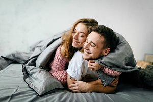 Couple in love having fun in bed and smiling. Artwork. Soft focus on the guy