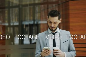 Stedicam shot of cheerful businessman talking with smartphone and walking in modern office hall