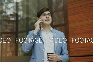 Panning shot of young businessman talking smartphone with cup of coffee in modern office