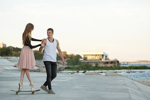 Ballerina on skateboard. Guy helps