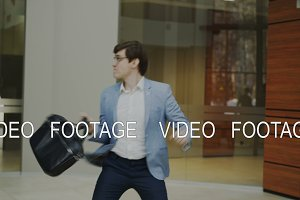 Happy and funny businessman with briefcase dancing in office lobby while nobody watching him