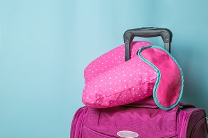 Traveling concept - pink suitcase in front of blue background