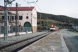 Train entering old railroad station platform in countryside