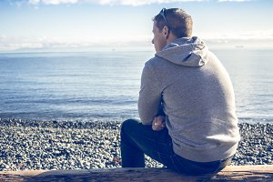 Man sitting looking out at ocean