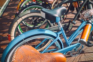 Many bikes in a row on the street. Bicycle parking. Colored bicycles on the street