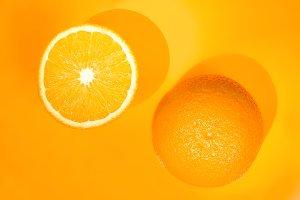Two oranges on orange background. Art food concept