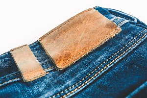 Denim background. Blue jeans with a brown leather label empty space