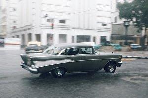 Old grey car runs along the street