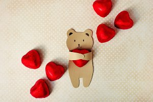 congratulations on the Valentine's Day. A small bear of kraft paper holds in his paws a chocolate candy in the form of a heart in a red foil