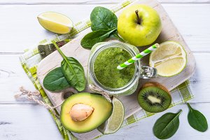 Green smoothie and ingredients on white wooden table.