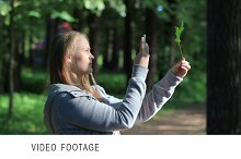 Young woman taking a picture of leaf