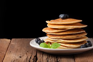 Pancakes with blueberries on a woode