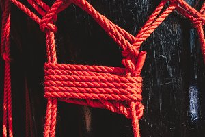 Knots from red ropes of taiko drums o-kedo close up background. Musical instrument of Asia