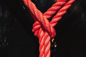 Knot from red rope of taiko drums o-kedo close up background. Musical instrument of Asia