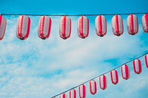 Paper red-white japanese lanterns Chochin hanging on blue sky background