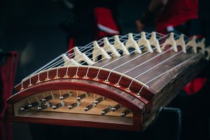 Musical String Instrument of easr asia koto yatga guzheng chinese zither, zheng, gayageum om dark background. Selective focus on picture