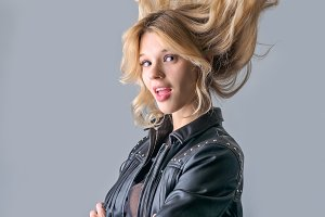 Young woman in a black leather rocker jacket.