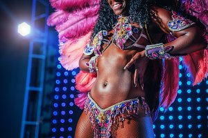 Beautiful bright colorful carnival costume illuminated stage background. Samba dancer hips carnival costume bikini feathers rhinestones close up.