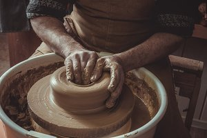elderly man making pot using pottery wheel in studio. Close-up.